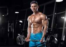 Indivíduo considerável novo que faz exercícios no gym fotografia de stock