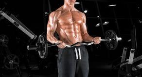 Indivíduo considerável novo que faz exercícios no gym imagem de stock