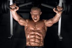 Indivíduo considerável novo que faz exercícios no gym foto de stock