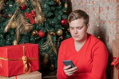 Indivíduo considerável que conversa no telefone novo que senta-se sob a árvore cercada por caixas dos presentes Natal e presentes imagens de stock royalty free