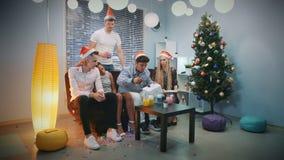 Indivíduo considerável que põe o gelo seco nos cocktail para amigos em chapéus de Santa sobre o Natal vídeos de arquivo