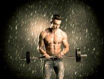 Indivíduo da aptidão com o peso que mostra os músculos fotografia de stock royalty free