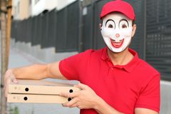 Indivíduo da entrega da pizza que veste uma máscara estranha imagem de stock