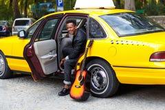 Indivíduo da felicidade assentado nos interiores do táxi, olhando um lado e sorrindo, com pé esquerdo fora, perto da guitarra, na fotografia de stock