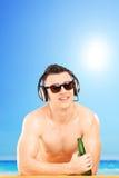 Indivíduo de sorriso com fones de ouvido e óculos de sol que bebe a cerveja Foto de Stock