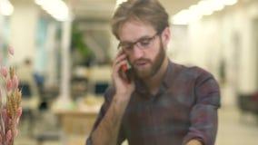 Indivíduo de sorriso farpado com vidros e a camisa de manta ocasional que fala em um telefone celular vídeos de arquivo