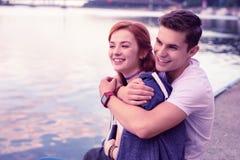 Indivíduo de sorriso forte que abraça firmemente sua amiga bonita do gengibre fotografia de stock royalty free