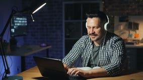 Indivíduo de sorriso que escuta a música com fones de ouvido usando o portátil no escritório na noite vídeos de arquivo
