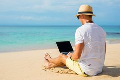 Indivíduo de vista ocasional que usa o portátil na praia Foto de Stock
