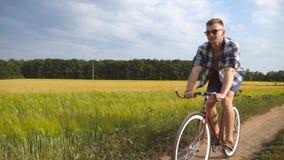 Indivíduo desportivo nos óculos de sol que dão um ciclo ao longo da fuga do país exterior Bicicleta de sorriso nova do vintage da filme