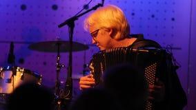 Indivíduo do albino que joga o acordeão na luz azul filme