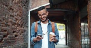 Indivíduo do Oriente Médio de sorriso que usa o ar livre do smartphone e guardando para ir café video estoque