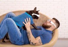 Indiv?duo dos esportes nos vidros 3D com seu c?o que encontra-se no sof? Olhe se fotos de stock royalty free