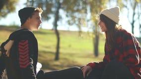 Indivíduo e menina do moderno para comunicar o assento na luz do sol no parque Os adolescentes estão relaxando fora Menina do ska filme