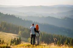 Indivíduo e menina felizes nas montanhas na manhã Foto de Stock