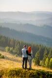 Indivíduo e menina felizes nas montanhas na manhã Imagens de Stock Royalty Free