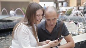 Indivíduo e menina que sentam-se na alameda no fundo da fonte que discute fotos no telefone e no riso vídeos de arquivo
