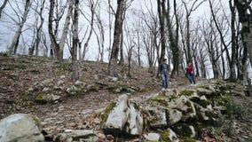 Indivíduo e uma menina para ir abaixo do trajeto rochoso na floresta calva filme