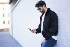 Indivíduo elegante em calças de brim leves, em um t-shirt branco e em um revestimento escuro Imagem de Stock