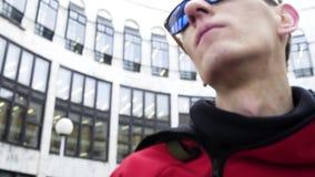 Indivíduo energético em danças vermelhas da roupa e dos óculos de sol do esporte ao lado das colunas do granito video estoque