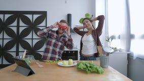 Indivíduo engraçado com a menina que engana ao redor e que ri ao cozinhar a salada na refeição matinal para o bem-estar de acordo video estoque
