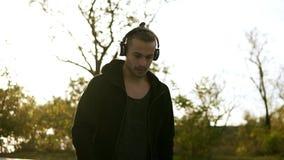 Indivíduo eriçado novo em ocasional preto e em fones de ouvido Homem da calma que põe sobre seus fones de ouvido e música de escu video estoque