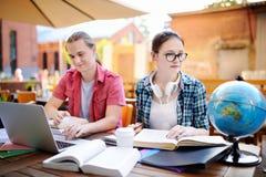 Indivíduo esperto e menina novos que fazem seus trabalhos de casa no campus universitário Imagens de Stock