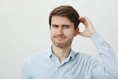 Indivíduo europeu ordinário confundido com a cerda que risca a cabeça ao olhar com frustração na câmera, sendo questionado ou fotografia de stock