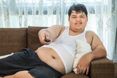 Indivíduo excesso de peso que senta-se no sofá para olhar alguma tevê Foto de Stock Royalty Free