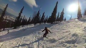 Indivíduo feliz em um esqui que desliza abaixo da inclinação no dia ensolarado filme