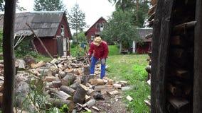 Indivíduo forte do aldeão que prepara o combustível de madeira natural e casas rurais 4K vídeos de arquivo