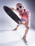 Indivíduo louco com um skate que faz as caras engraçadas Foto de Stock Royalty Free