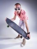 Indivíduo louco com um skate que faz as caras engraçadas Imagens de Stock
