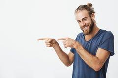 Indivíduo maduro alegre com a barba que levanta para o artigo no jornal da universidade que aponta de lado com os dedos em ambas  imagens de stock royalty free