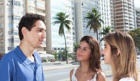 Indivíduo mexicano novo que fala com as duas amigas na cidade imagens de stock royalty free