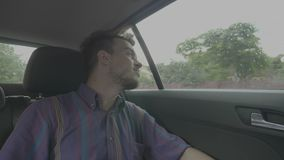 Indivíduo milenar focalizado do homem que olha fora da janela à vista urbana que viaja pelo carro do uber através da cidade no di video estoque