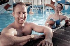 Indivíduo milenar relaxado que inclina-se na borda da piscina fotos de stock royalty free