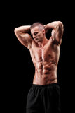 Indivíduo muscular considerável que levanta no fundo preto Foto de Stock
