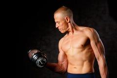 Indivíduo muscular do halterofilista que faz exercícios com peso sobre o fundo escuro foto de stock