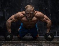Indivíduo muscular do halterofilista sobre o fundo escuro fotografia de stock