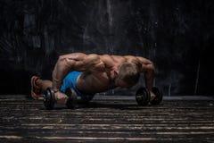 Indivíduo muscular do halterofilista sobre o fundo escuro imagem de stock royalty free