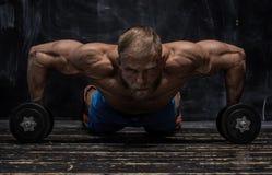 Indivíduo muscular do halterofilista sobre o fundo escuro fotografia de stock royalty free