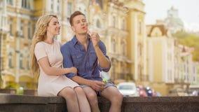 Indivíduo no amor que faz as bolhas de sabão, amiga no amor que senta-se ao lado dele, data fotos de stock royalty free