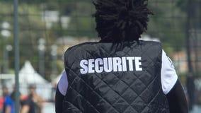 Indivíduo no revestimento preto da segurança que senta-se para trás na frente do campo de esporte, close-up filme
