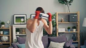 Indivíduo nos vidros da realidade virtual que encaixotam em casa as mãos moventes que aprecia a atividade video estoque