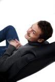 Indivíduo novo amigável na cadeira que olha o Fotografia de Stock Royalty Free