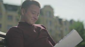 Indivíduo novo de sorriso que senta-se com um livro em um banco video estoque
