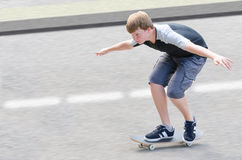 Indivíduo novo do adolescente do skater no movimento que move sobre o skate Foto de Stock