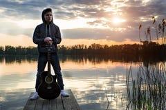 Indivíduo novo em uma capa que está com sua guitarra na ponte na noite contra o contexto de um por do sol no rio Imagem de Stock