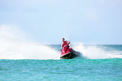 Indivíduo novo que cruza em um esqui do jato no mar das caraíbas Fotos de Stock Royalty Free